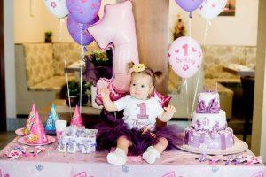 Малката Ая с бебешки комплект за рожден ден в лилаво и жълто